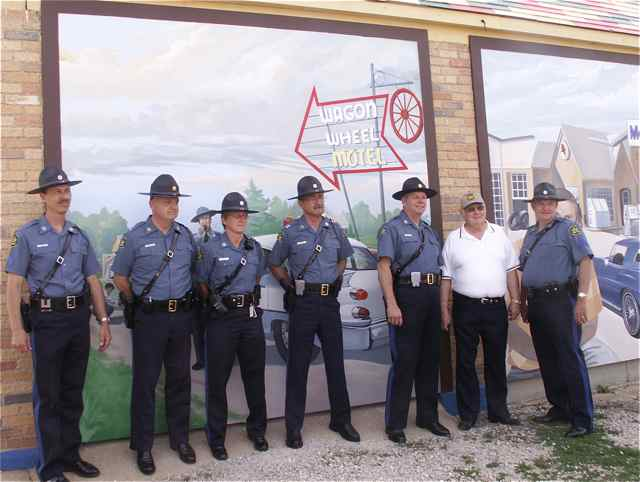 Retired Sergeant Woody Aytes poses with some other troopers in front of the Rt. 66 Panel at the History at the 4-Way mural.