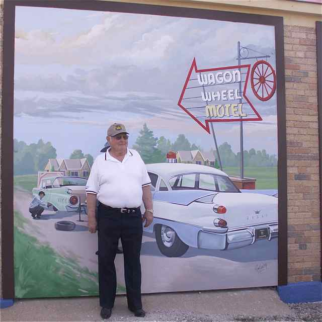 Sergeant Woody Aytes posing in front of the Rt. 66 mural that featured a vintage patrol car with number 85 on the license plate.