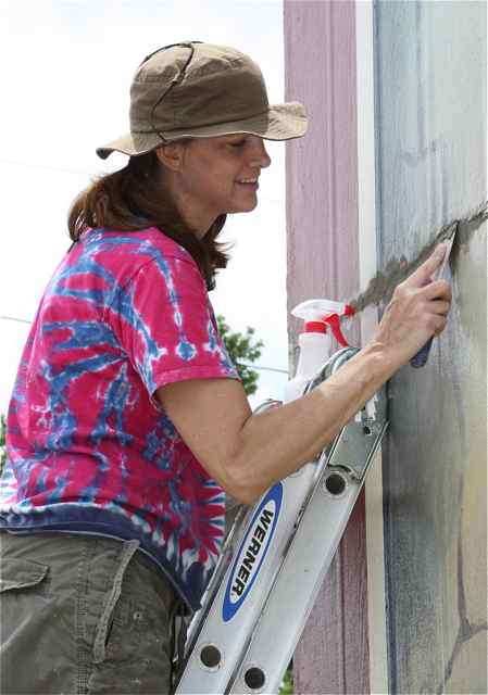 Artist and teacher Steiger does maintenance work on the Amelia mural during the summer.