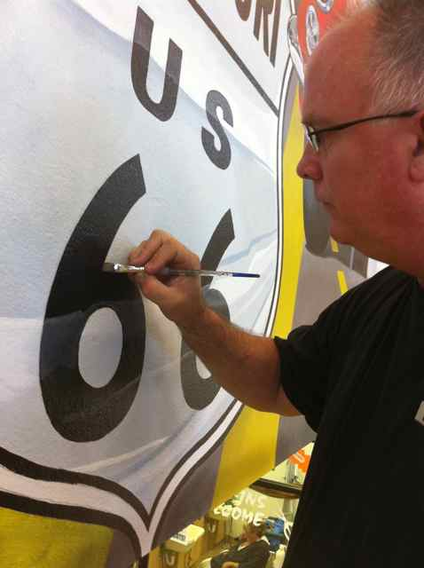 At the midpoint of painting, Harvey painted the Rt. 66 shield on the mural. He took this photo himself--a tricky shot.